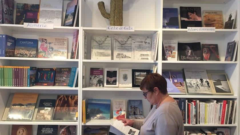 La librera echa un vistazo a una de las obras de su sección dedicada a Cabo de Gata.