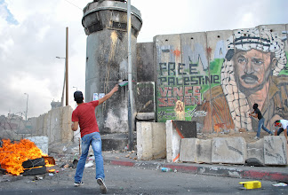 Photo: A Palestinian youth begins throwing rocks at a watchtower stationed by Israeli soldiers.
