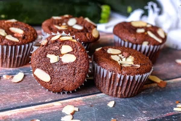Six Chocolate Zucchini Muffins With Slivered Almonds On Top.