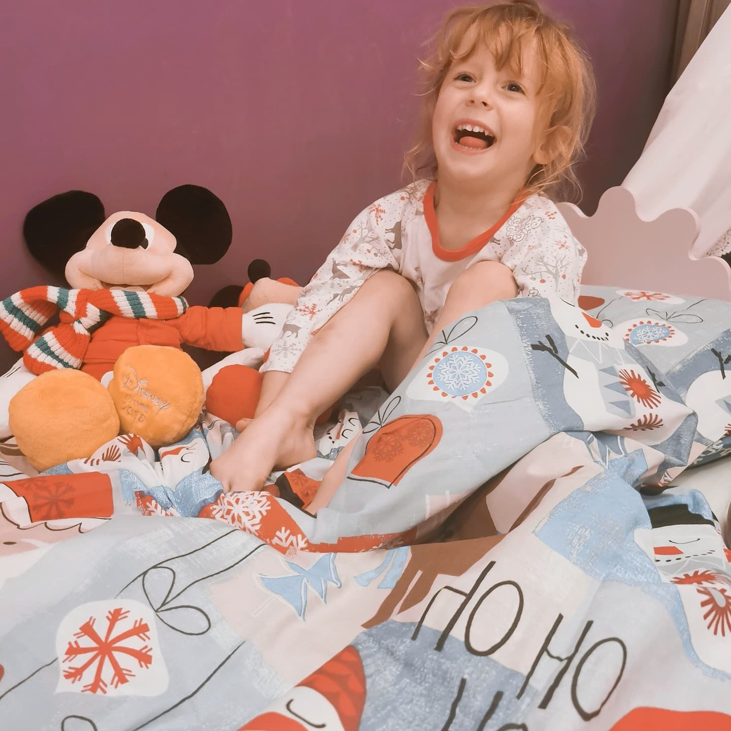 A child lying on a bed in Santa Christmas bedding with stuffed animals.
