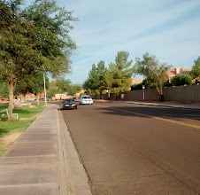 "Photo: Knox Rd, west of Rural, Tempe. Fairly common collector street configuration. The road is laned, in this case, just with a center line. This road is a ""two-lane highway"". The lanes are quite wide, perhaps 18 feet, each; however parking is allowed. The darker car is parked (not particularly well). When no cars are parked, and no other obstructions, each lane is ""wide enough to share"" safely, and so bicyclists going slower than the ""normal speed of traffic"" must ride ""as close as practicable"" to the right-hand curb. On the other hand, any parked vehicle narrows the lane to the point where it is clearly not wide enough to share; and 815A4 exception would apply and cyclists can ride anywhere within the right-half of the roadway."