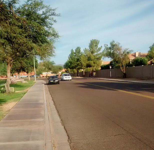 """Photo: Knox Rd, west of Rural, Tempe. Fairly common collector street configuration. The road is laned, in this case, just with a center line. This road is a """"two-lane highway"""". The lanes are quite wide, perhaps 18 feet, each; however parking is allowed. The darker car is parked (not particularly well). When no cars are parked, and no other obstructions, each lane is """"wide enough to share"""" safely, and so bicyclists going slower than the """"normal speed of traffic"""" must ride """"as close as practicable"""" to the right-hand curb. On the other hand, any parked vehicle narrows the lane to the point where it is clearly not wide enough to share; and 815A4 exception would apply and cyclists can ride anywhere within the right-half of the roadway."""