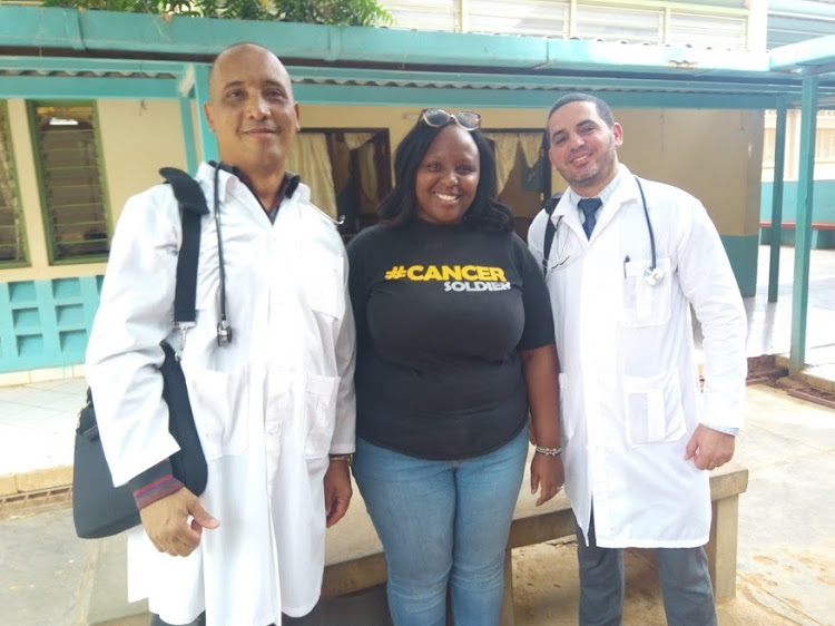 Dr Assel Herera Correa (general physician) and Dr Landy Rodriguez (surgeon) pause for a photo with Royal Media Services Staff Njeri Ngugi