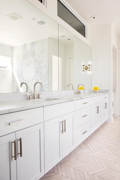 large white modern bathroom with white shaker cabinets, chrome hardware, double wide wall mirrors and double sink