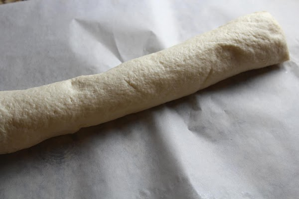 Open the can of Pillsbury® thin pizza crust and remove the dough.