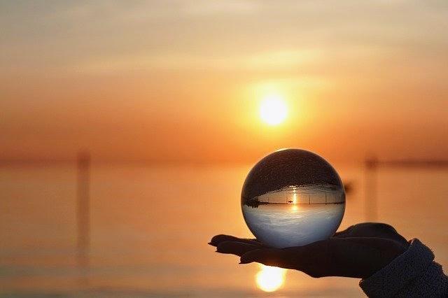 イメージ写真。夕暮れ海をバックに手にはガラス玉