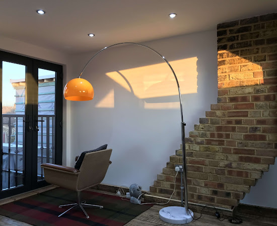 a modern loft with a reading lamp standing over a chair