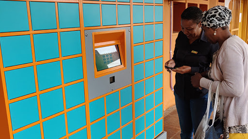 A health worker assists a patient who is about to use the Pelebox smart locker.