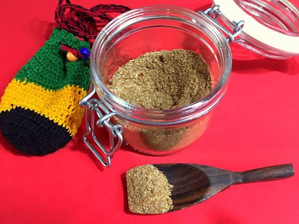 A Spice Blend In A Jar With A Wooden Spoon In Front.