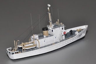 """Photo: Rear 3/4 starboard view. Electrical conduit, drip rails, whip antennae, ladders, stairways, and many other details are separately applied and accurate to scale. The 125' Active class cutters served from the late 1920s into the 1970s. This exquisitely detailed model shows a later configuration, with fewer scuppers (portholes) along the length of the hull, and custom photo-etched railings with correct stanchion spacing. Also available in a full hull model. This little gem is only 9.4"""" long and will fit even in small harbors or riverside scenes. Every detail is meticulously to scale."""