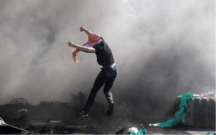 2021年5月18日,在以色列占领的约旦河西岸纳布卢斯附近的哈瓦拉检查站附近,一名巴勒斯坦人在反以色列抗议活动中跳到一个用轮胎制成的路障旁。