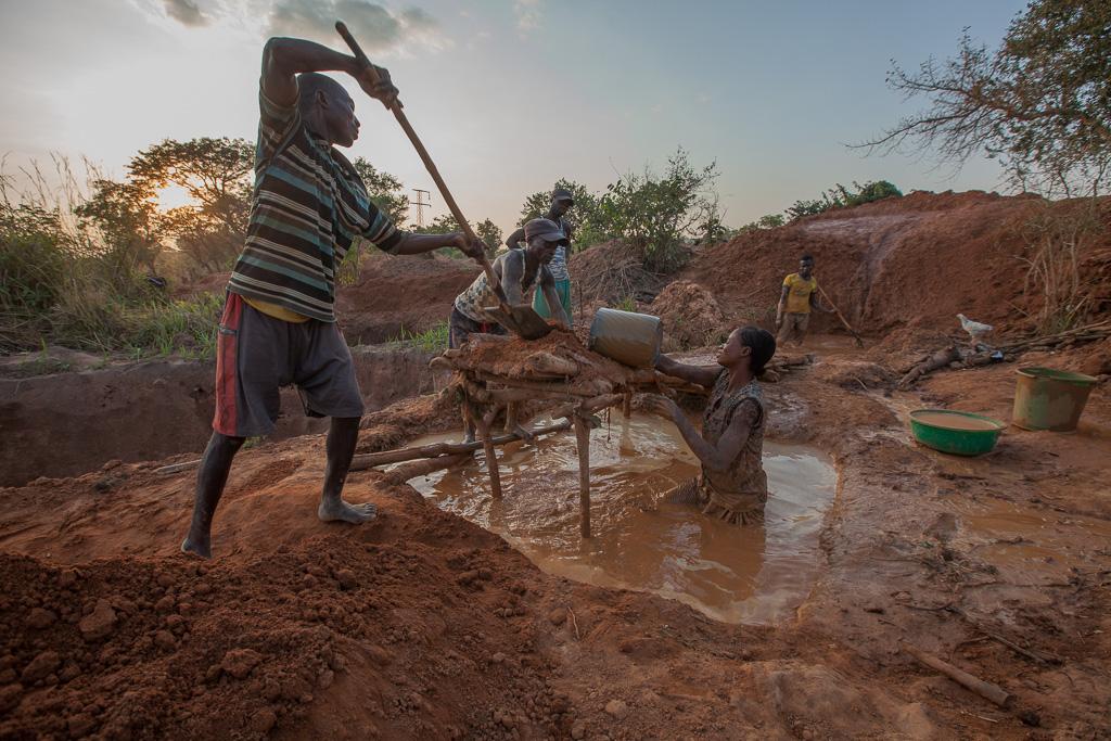 道具を使って泥と土をふるいにかける 5 人の人々。