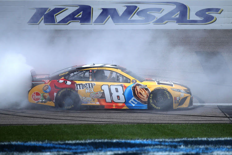 Kyle Busch, driver of the #18 M&M's Mix Toyota, celebrates with a burnout after winning the NASCAR Cup Series Buschy McBusch Race 400 at Kansas Speedway on May 02, 2021 in Kansas City, Kansas.