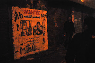 Photo: Men look at a graffiti-made 'Wanted' sign identifying a police officer that was captured on a widely circulated online video shooting a protester in the eye.