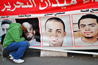 Photo: A protester mourns at the sight of a loved one on a banner portraying several martyrs of the Egyptian revolution.