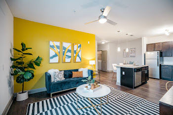 Model living room with wood-inspired flooring and yellow accent wall