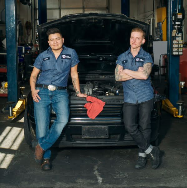 Two LGBTQ+ mechanics lean back on the open hood of a car at a repair shop