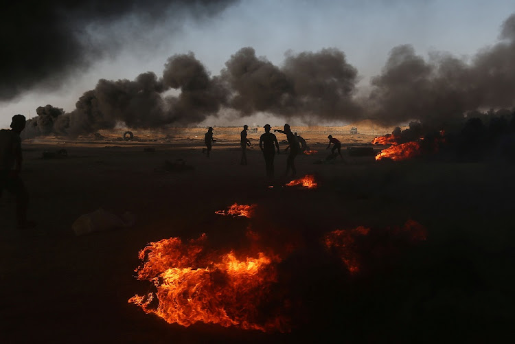 Palestinian demonstrators stand near burning tyres at the Israel-Gaza border in the southern Gaza Strip. Israel is detested not for what it does but for what it is, says the writer. Picture: REUTERS