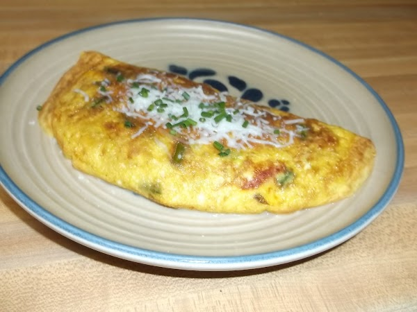 Use a spatula to fold omelette in half. Sprinkle with remaining 1/2 tablespoon Italian...