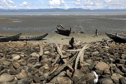 A child walks past remnants of boats — destroyed by the Bangladeshi government — that were used to ferry Rohingya refugees fleeing violence in Myanmar, at Shah Porir Dwip near Cox's Bazar, on October 4 2017. Picture: REUTERS