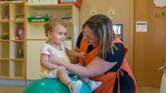 Una niña realiza ejercicios de estimulación bajo la atenta mirada y el apoyo de una educadora