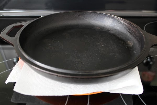 Cast iron pan placed on top of steaks.