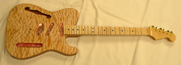 Photo: Quartersawn maple neck with a tung oil finish. Double-acting truss rod, adjusted at the heel. Grover locking tuners. Grounded copper shielding.