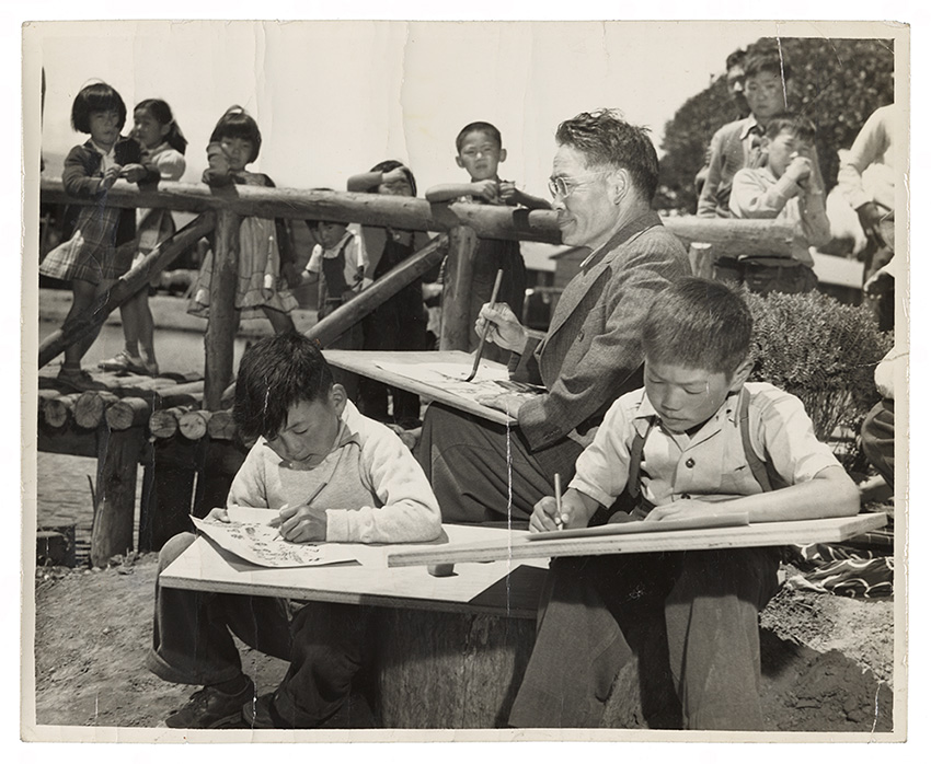 Artist Chiura Obata teaching a children's art class outdoors at Tanforan Assembly Center. There are two boys sitting on a tree stump drawing or painting on paper in the foreground. Obata is seated directly behind them, painting with an ink brush. In the background are about 8 more children of standing on a wooden bridge and watching.