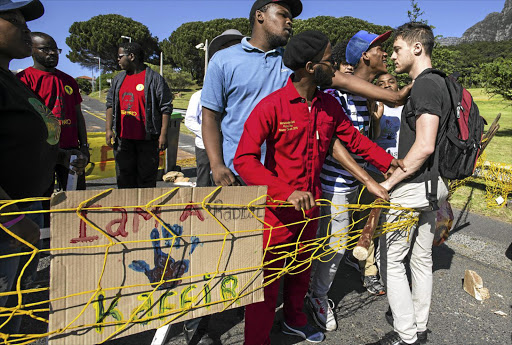 Black students at the University of Cape Town confront a white colleague during recent protests on the campus; the author says anti-white sentiment is mushrooming at universities, rooted in the writings of Frantz Fanon.