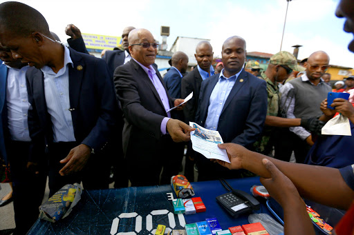 A vendor lights a cigarette, seemingly unmoved by the hubbub created by President Jacob Zuma's visit to Marabastad near Pretoria. The president wanted to find out what he should say on Thursday in his state of the nation address in Cape Town.