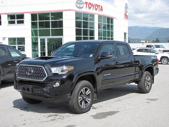 A black Toyota Tacoma sits parked in front of Castlegar Toyota
