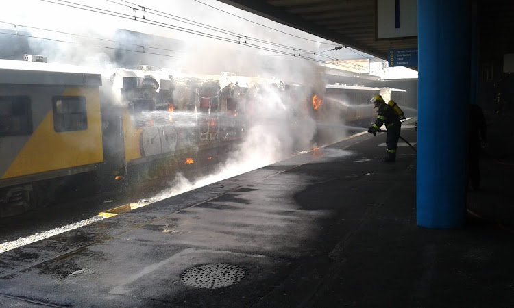 A fireman tackles the burning train at Cape Town station