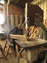 """Photo: A la scie à ruban, Michel découpe les varangues. Une quinzaine dans la journée... Entre 20 et 50 kg le bout. """"Je vais quand même bien dormir ce soir !..."""""""