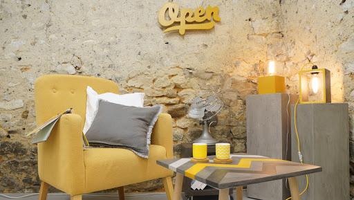 ambiance gris et jaune moutade avec tabe d'appoint en béton ciré aux motifs aztèques et au style design
