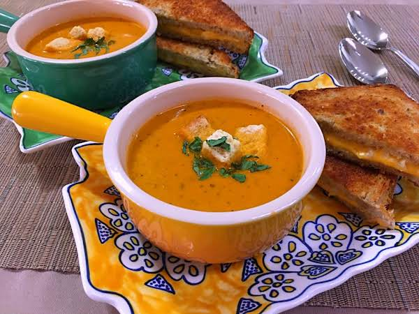 Two Bowls Of Tomato Soup Along With Grilled Cheese Sandwiches.