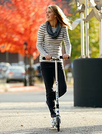Woman riding kick scooter in the fall