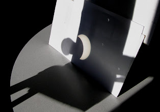 Photo: Wide angle view of projection, Large Circle to the left is the table top, paper slanted in the middle, open side of binoculars on left, cardboard over right binocular for dark background