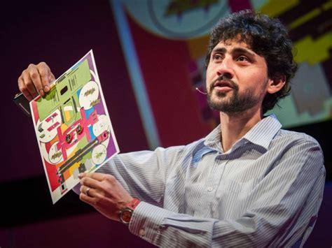 Le fondateur du Foldscope lors d'un discours, tenant un microscope low-tech qui consiste en une feuille de papier multicolore.