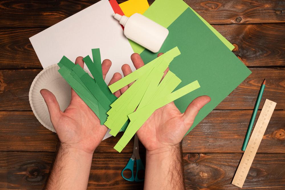 Vários papeis coloridos recortados para simular uma árvore de natal.