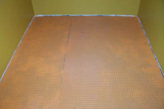 "Photo: After the floor's surface was as clean as I could get it, I rolled out an uncoupling material called Schluter-Ditra. It's a polyethylene plastic underlayment that has a waffle pattern on the surface. The little ""waffle-wells"" get filled up with mortar, making a strong and flexible underlayment for ceramic or porcelain tile. In this picture, you can see the dark spots of thinset mortar soaking into the fleece backing of the Ditra. This is what's supposed to happen, so I think I'm doing good so far! *fingers crossed*"