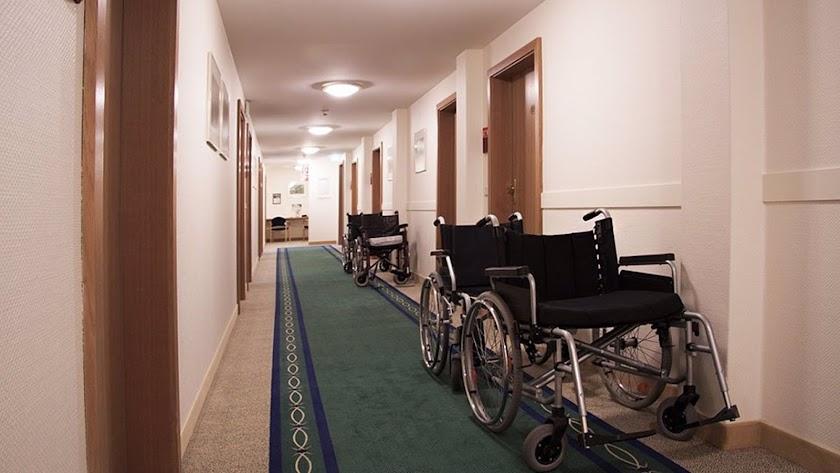 Sillas de ruedas junto a las puertas de las habitaciones en una residencia de mayores.