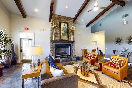 Clubhouse lounge area with a couch, coffee table, two orange accent chairs, and a fireplace