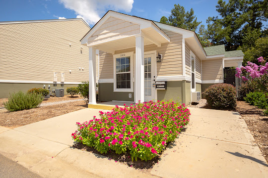 Leasing office with neutral exterior, a covered entrance, and floral landscaping