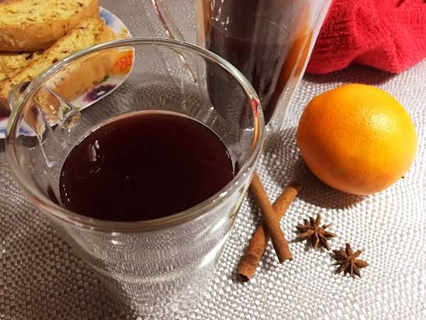 A Glass Filled With Cider Sitting On A Beige Table Mat Along With Cinnamon Sticks, Star Anise, Orange, Red Napkins And Biscotti.