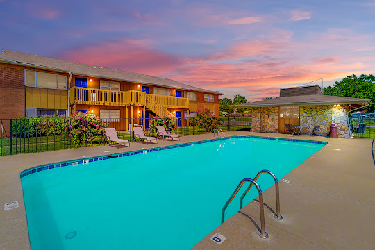Meadowbrook Apartments swimming pool surrounded by concrete and fence and clubhouse