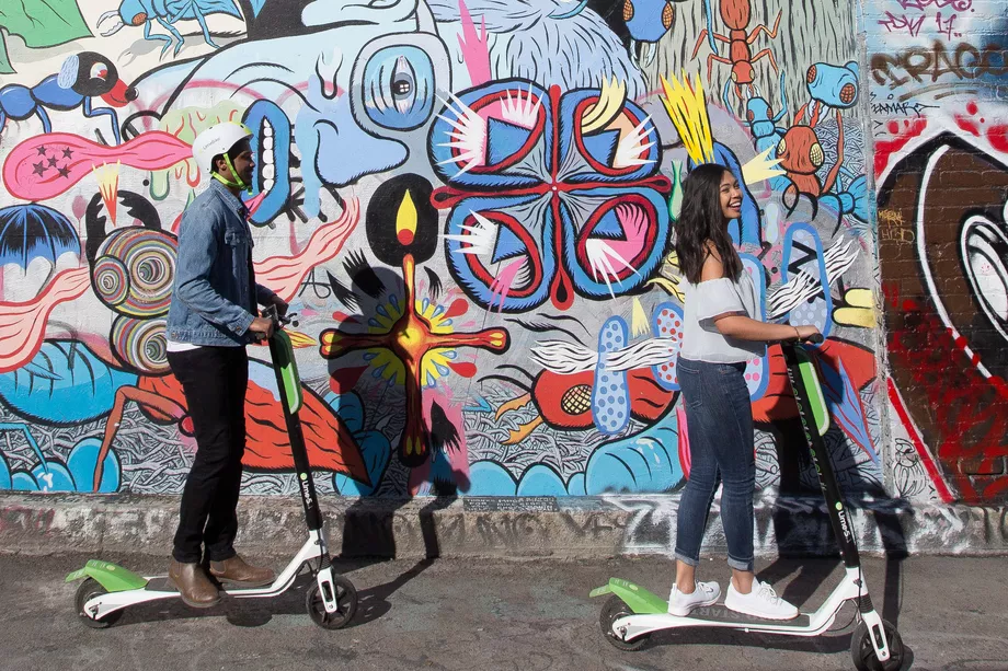 Couple riding on Lime e-bikes with mural background