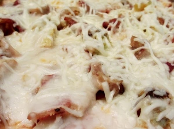 Spread pizza sauce over cooled crust, add toppings and cheese. Dust lightly with garlic...