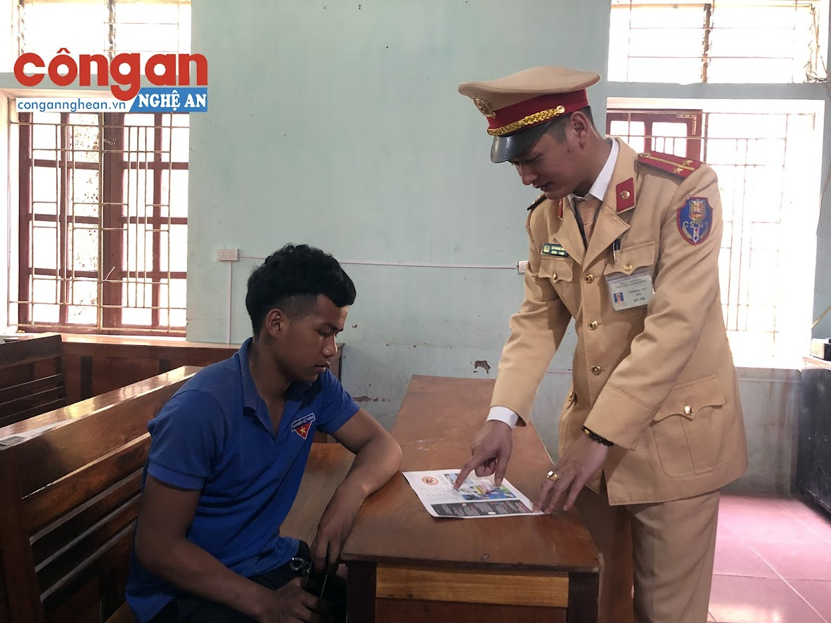 Cảnh sát giao thông hướng dẫn một thanh niên phân biệt các biển báo giao thông