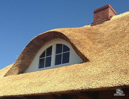 Wole oczko na dachu ktytego świeżą żółtą trzciną na tle bezchmurnego nieba