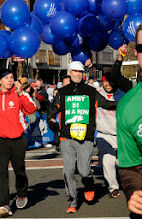 Photo: MANCHESTER 11/28/13  Amby Burfoot acknowledges the crowd as he finishes his 51 st Manchester Road Race in a row, setting the all time record. For the final few meters he was surrounded by 51 balloons so the crowd could follow his finish. (MRR Photo by John Long)